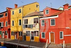 Photo taken on the island of Burano in the village of fishermen and lace embroiderers in the municipality of Venice Italy. In the picture you see, in the foreground, a house Corner taken with facades of dark red color. To the left you see other houses of colors and different shapes. in front of the façade of the small yellow and there are clothes to dry.