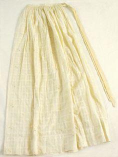 Förkläde. Av vitt bomullstyg, rutigt med spridda blommotiv i skärt och grönt. Smal dragsko upptill.