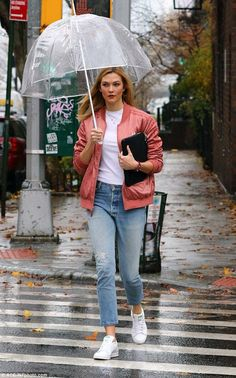 Brand ambassador: Karlie Kloss braved the rain Wednesday wearing a pretty pink Adidas bomber jacket and coordinating white and green tennis shoes