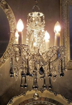 Vintage brass chandelier is painted shimmery silver metallic. Old metal flowers have been attached at the top and center and are also silver metallic, with each having a vintage Austrian crystal rhinestone at its center.  This four~arm fixture is draped in clear and silver metallic faceted crystal bead strands ~ top to bottom. The four arms are surrounded with alternating clear and silver water drop crystal prisms. The upper bobeche is surrounded with tiny vintage teardrop prisms, the center…