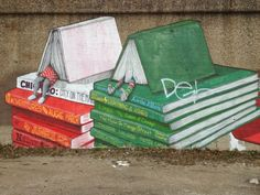 Pilsen Books. This book-themed mural is a part of an ongoing street art project by Chicago-based creative collective, Pawn Works. The mural was painted in Chicago, on a lengthy old wall in Pilsen neighborhood.