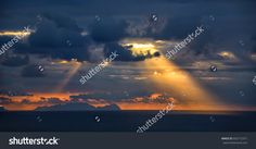 At sunrise, the sun rays shine through the clouds to the ocean. Portugal, Madeira Island.
