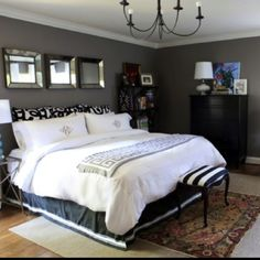 Black furniture with gray walls and white ceiling.  Room is lightened by white comforter, lighter colored rug, and wood flooring.