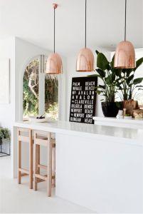 Minimal bir mutfağı sıra dışı kılmanın en yaratıcı yolu, tavandan sarkan bakır lambalar.