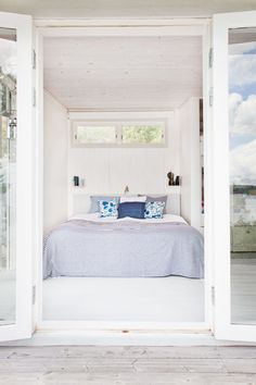 Tiny Bedroom in Swedish Cottage I Remodelista: Summer cottages are typically tiny with little wiggle room in the bedrooms. Skip the bedside tables and instead use a favorite Scandi device: wall shelving as storage. Ideas Terraza, White Washed Floors, Swedish Cottage, Red Cottage, Beach Cottage Style, Beach House, Coastal Style, Floor Decor, Beautiful Bedrooms