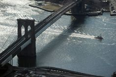 BROOKLYN BRIDGE WITH A TUB BOAT PASSING THRU AS SEEN FROM THE FREEDOM TOWER LOOKING DOWN