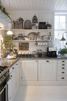 White shiplap walls and deep-gray stone counters set the tone for vintage accessories in this French country-cottage kitchen.