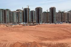 Two workers walk along a megablock development in Kangbashi, the new district of Ordos in Inner Mongolia.