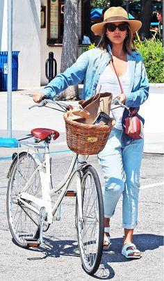Jessica Alba wears a striped tank top, denim jacket, cuffed jeans, white Birkenstocks, a crossbody bag, and a straw fedora