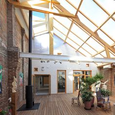 Le jardin d'hiver est commun aux deux ateliers. Il bénéficie de beaucoup de lumière, grâce à la verrière zénithale en polycarbonate alvéolé. Au sol un plancher en ipé (bois exotique) ; les murs sont en briques d'origine.