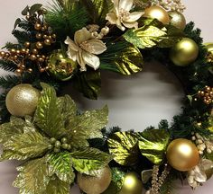 Oval Christmas wreath decorated with cream magnolia faux flowers and olive green metallic leaves.