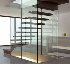 Modern glass and wood staircase design is done by Siller .