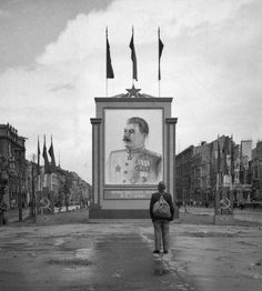 A German civilian looks at a newly placed poster of Stalin on the Unter-den-Linden in Berlin, 1945.