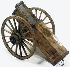Hiya-taihou (fire arrow cannon), 19th century, iron on a wooden carriage, with an applied copper triple oak leaf mon. Length of barrel 40.8cm., bore 8.54cm., total length including carriage 143cm., diameter of wheels 67.5cm.