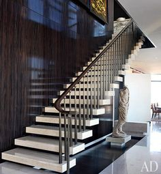 Travertine stairs appear to float next to an ebony-paneled wall in the gallery of a Manhattan duplex designed by architect Carlos Aparicio. A Roman togatus statue and 1924 gold-leafed murals by José María Sert offset the modernity of the staircase. Interior Staircase, Staircase Railings, Staircase Design, Stairways, Architectural Digest, Duplex Design, Escalier Design, Stair Handrail, Cantilever Stairs