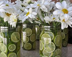 Daisies centerpiece with limes in mason jar. Good centerpiece ideas...different flowers for different times of year. What about sunflowers in quart jars with oranges for fall?