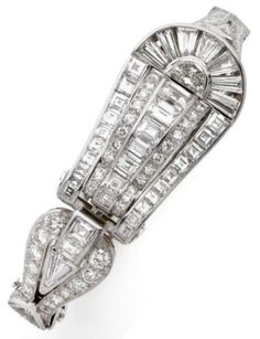 A RARE ART DECO PLATINUM AND DIAMOND BRACELET Shadowing A WATCH, CIRCA 1930. The diamond-set platinum bracelet opens to reveal a watch. Mechanism signed Milus.