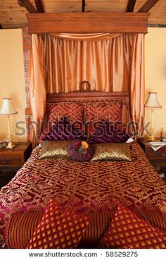 stock photo : romantic luxurious bed with red brocade and purple velvet and canopy