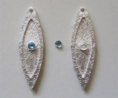 Silver marquise earring drops embedded with commercial fine silver bezel cups before firing, to be set with calibrated natural blue topaz cabochons after firing.