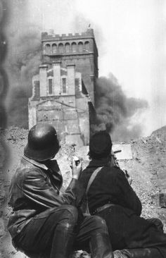 "Warsaw Uprising: Insurgents from ""Kiliński"" Battalion on barricade at Zielna street watch burning PASTa building at 37/39 Zielna Street."