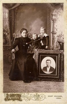The deceased father included in this picture on a large framed photograph. Mother and children still in mourning cloths.