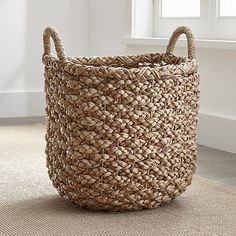 Shop Emlyn Basket.  Chunky braids of rustic bankuan leaves weave a tall textural basket, ready to stow toys, towels, magazines and more.  Sturdy handles are soft to the touch but strong enough for carting stored items.