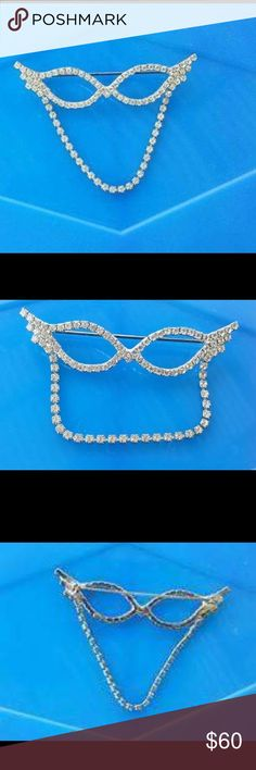 """VTG 1950s Rhinestone Cateye Eyeglass Holder Pin Vintage 1950s cat eyeglass holder pin/brooch in the shape of cat eyeglasses. Silver tone embellished w/clear rhinestones. Pin on back so this can be pinned onto your top and your eyeglasses (or sunglasses) are held in place with the looped chain on front. A stunning & unique original vintage 50s piece.  DETAILS: PRICE IS FIRM.  Size: App 3"""" in width, 2"""" in length (including the chain that hangs down from it)  Era: 1950s Vintage Condition: EX…"""