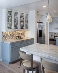 An X shaped mullion pattern on a glass cabinet door is beautiful and classic for transitional kitchens. Colorful Kitchen design with blues, grays and white featuring Dura Supreme Cabinetry.