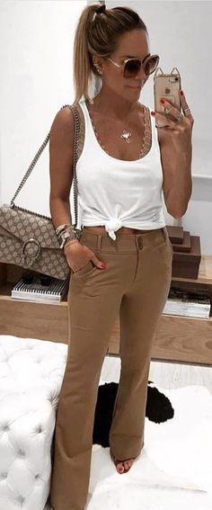 #spring #outfits woman wearing white tank top and brown pants holding iPhone. Pic by @milano_streetstyle