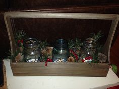 Bought this rustic wooden container and garland at Joann's for 70% off yesterday! I cut the garland and threw in some pine cones to fill the space around the mason jars I already had. I read someone else's post and used some Epsom salt I found in my cabinet to look like snow at the bottom of the jars and got some led tea light candles at dollar tree to go inside as well!