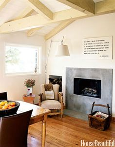 The geometric cement fireplace was custom-built to fit in this small space. Cream walls open up the room and reflect light.