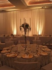 Candelabra vases on table with white amaryllis centerpiece
