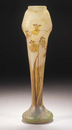 A DAUM CAMEO AND ENAMELLED GLASS VASE - the frosted glass internally mottled with yellow and orange towards base, etched and enamelled in yellow, brown and green with flowers, cameo mark Daum Nancy with a cross of Lorraine -- 48.5cm. high.