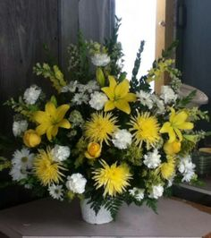 Funeral arrangement made by Brandis bouquets with carnations, lillies, roses, daisies, and spider poms.