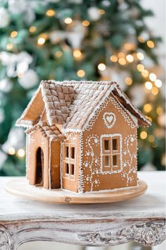 A simply decorated gingerbread house on a wooden table. Decorating with Gingerbread is a Christmas tradition. Head to Always the Holidays to learn more about The History of Gingerbread. #gingerbread #christmastraditions #funfacts
