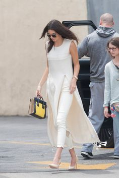 Kendall Jenner wears white pants, a long white tank top, matching pumps, aviator sunglasses, and a Céline bag