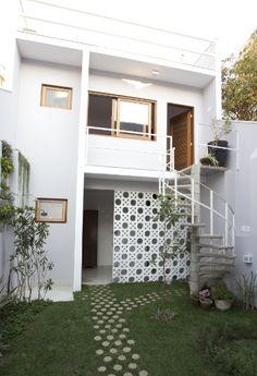 DEPOIS - Um volume da edícula, nos fundos do quintal, tem lavanderia e área de serviços no térreo e escritório no pavimento superior. A fachada é executada com elementos vazados (Neorex) que permitem a ventilação da área de trabalhos domésticos. Também há uma escada caracol em concreto, que leva ao escritório, e é antecedida por um caminho composto de blocos drenantes (Neorex). O projeto de reforma do sobrado na Liberdade, em São Paulo, é do escritório SET Arquitetura