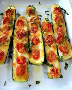 Slice the zucchini in half. Slice off the bottom to keep in stable. Brush with olive oil and top with garlic or garlic powder. Top with sliced tomatoes, fresh basil, salt and pepper to taste. Use mozzarella cheese, Parmesan cheese or mixed blend.. Bake 375 for 20 to 30 minutes until soft.