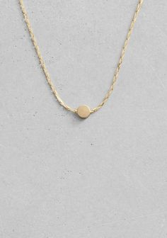 A delicate chain necklace featuring a free-moving bead.