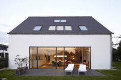 Ein Haus mit großen Fensterfronten, moderner Einrichtung und…