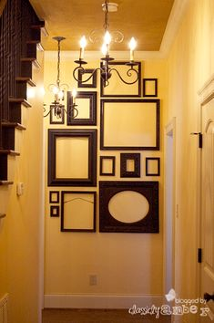 A wall of frames by DIY blogger Classicly Amber creates an architectural focal point in this cheerful yellow entryway. See her tutorial at classiclyamber.com | thisoldhouse.com