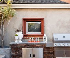 Concrete countertops, which are ideal for an outdoor kitchen, flank a stainless-steel grill. They serve as the perfect spot for preparing veggies for grilling or an impromptu buffet. A built-in niche above the cooking area houses a TV for outdoor viewing.