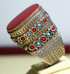 Silver Turcoman tower ring, decorated with turqoise and coral bits on the sides and a carnelian on its face. JL Coll.