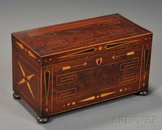 Inlaid Mahogany Tea Caddy, 19th century, likely sailor-made, with inlaid heart, arrows, geometric and shaped devices, and decorative stringing, with hinged lid opening to two lift-out inlaid mahogany compartments with hinged lids flanking a colorless cut glass mixing bowl, all raised on bun feet, ht. 6 3/4, wd. 12, dp. 6 in.
