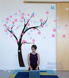 "Our Cherry blossom Tree wall decal looks as if it is blowing in the wind.  It measures as shown here 70"" tall by 84"" wide. The tree alone measures 66"" tall by 53"" wide.  You can get this lovely design in up to 4 colors  1. tree  2. Blossoms 1  3. Blossoms 2  4. Birds  This is a decal kit, you wil..."