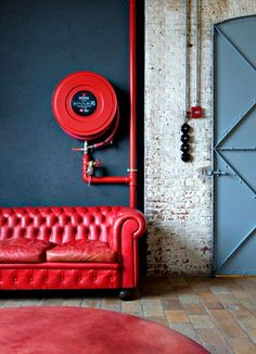 Gorgeous statement-making rooms and interior design inspiration featuring striking red furniture, art, accents, and moments throughout, like this classic Chesterfield sofa in red leather against the fire hose and red area rug below.