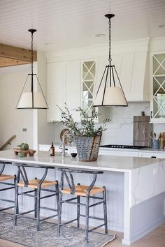 Gray Persian rug with gray wishbone bar stools at a kitchen island balance together around white cabinetry to create a cozy, homey, modern farm house.