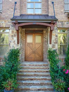 Front Stairs and Entryway on a Brick and Stone Home The brick and stone exterior of this home supports a sturdy awning made from wood and metal. Brick stairs lead to the double front door featuring frosted windows and transoms. Front Door Overhang, Front Doors With Windows, Wood Front Doors, Front Door Entrance, Entrance Decor, Front Entrances, Front Porch, Front Entry, Porch Awning