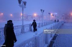 Warmly dressed locals walk across an ice-coated bridge in the center of Yakutsk. Photo: Amos Chapple