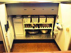 キッチンシンク下収納 ラックを上手に使って。扉にもフックを取り付けてデッドスペースを活用しています。